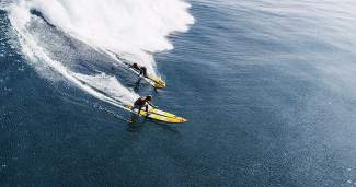 Pro paddleboarders Robby Naish and Kai Lenny ride a wave in Maui for the Breck Film Fest selection