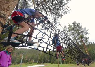 A mom helps her son get started on the rope net obstacle during the first-annual Copper Family Adventure Quest on July 2.