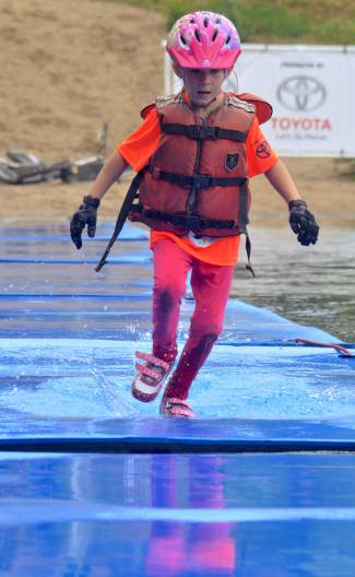 A young racer runs along floating pads during the Copper Family Adventure Quest on July 2. The first-annual event pitted parent-child teams against obstacles like the pond crossing, a river crossing and mud pits.