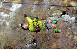 A parent pulls himself along the suspended river crossing obstacle during the first-annual Copper Family Adventure Quest on July 2.