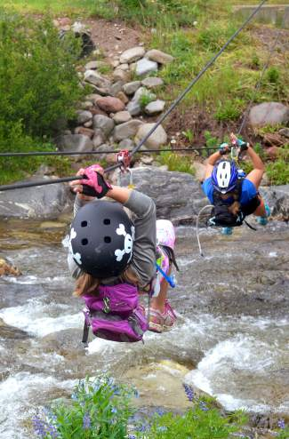 A mother-daughter duo traverses a creek via ropes during the debut of the Copper Family Adventure Queston July 2.