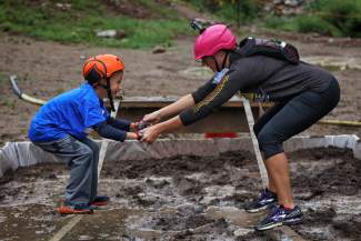 A mother-son duo carefully navigates the mud pit at the first-annual Copper Family Adventure Quest, a family-friendly adventure race held at Copper Mountain on a rainy July 2.