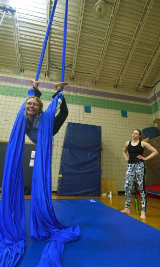 The author sees how far she can bend between aerial silk sheets as instructor Rachel Miller looks on during an intro session at the Breckenridge Recreation Center in January.