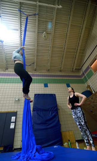 The author practices moves high on the silk sheets during an aerial silk course with instructor Rachel Miller (right) at the Breckenridge Recreation Center in January.