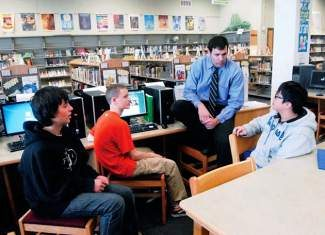 Summit Middle School principal Joel Rivera sits and chats with a trio of students from left, Alex O'Neal, Logan Gregory and Raiden Nguyen in the school library in 2012. Amendment 66 proposes new funding for public schools with an income tax increase.
