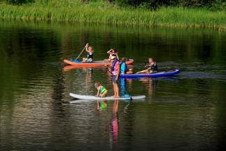 A family tries out stand-up paddleboarding recently in Summit County.