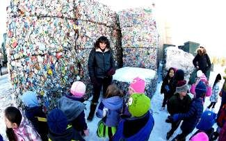 Jen Santry, Community Programs Director at HC3, gives a school tour of the source separated recycling bales at the Summit County MRF.