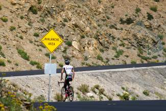 Australian cyclist Lachlan Morton passes an avalanche danger sign in the final few miles of the Loveland Pass road route. Road rides are one of the few options for cyclists during mud season in Summit County, when most mountain bike trails are still to sloppy for bikes.