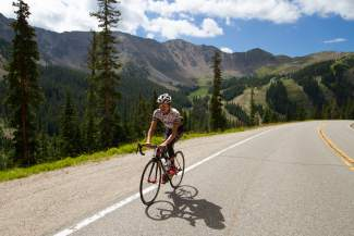 Jelly Belly-Maxxis team cyclist Lachlan Morton begins climbing the steepest section of Loveland Pass with the lush, green slopes of Arapahoe Basin in the background.