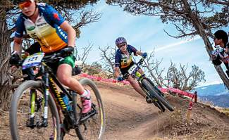 Ezra Smith (front) takes a berm with Salida's Harper Powell tight on her tire during the varsity girl's race at the Colorado High School Cycling League State Championships on Oct. 24 in Eagle.