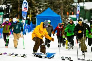 A snowboarder scrambles to clip in at the start of the Arapahoe Basin Enduro in 2015. From 7 a.m. to 5 p.m., the annual event pits 35 teams of two people each against the toughest terrain found off Pallavicini Chair on the west edge of the ski area.