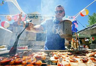 Austin Edminsson of the Golden Toad seasons shrimp and sausage skewers with sauce during the Colorado BBQ Challenge in Frisco Saturday, June 18, 2016.