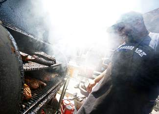Rat Jr. mans the grill at Rat's Woodshack BBQ during the Colorado BBQ Challenge in Frisco Saturday June 18, 2016.