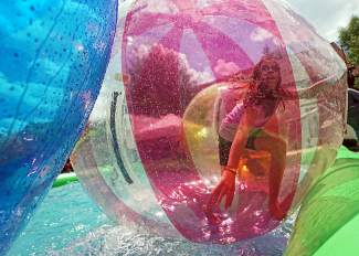 Brianna Keese, 10, of Silverthorne runs inside an inflatable water ball during the Colorado BBQ Challenge in Frisco Friday, June 17, 2016.