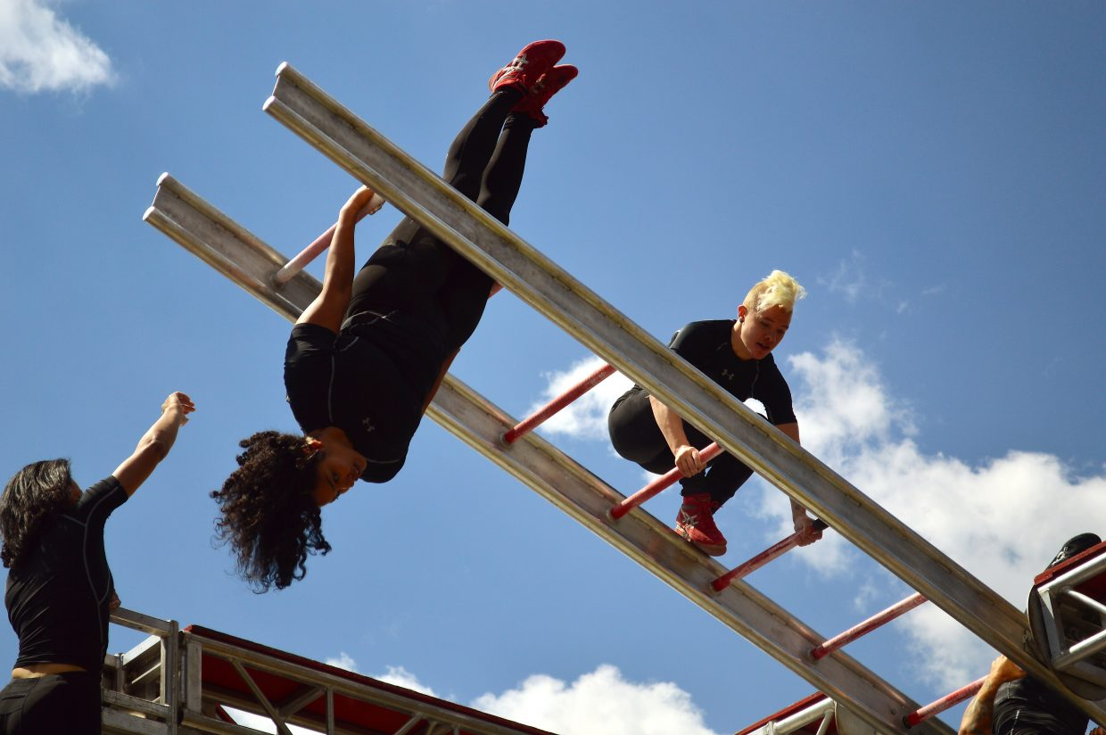 STREB action hero Cassandre Joseph clings to the spinning ladder in front of the Riverwalk Center.
