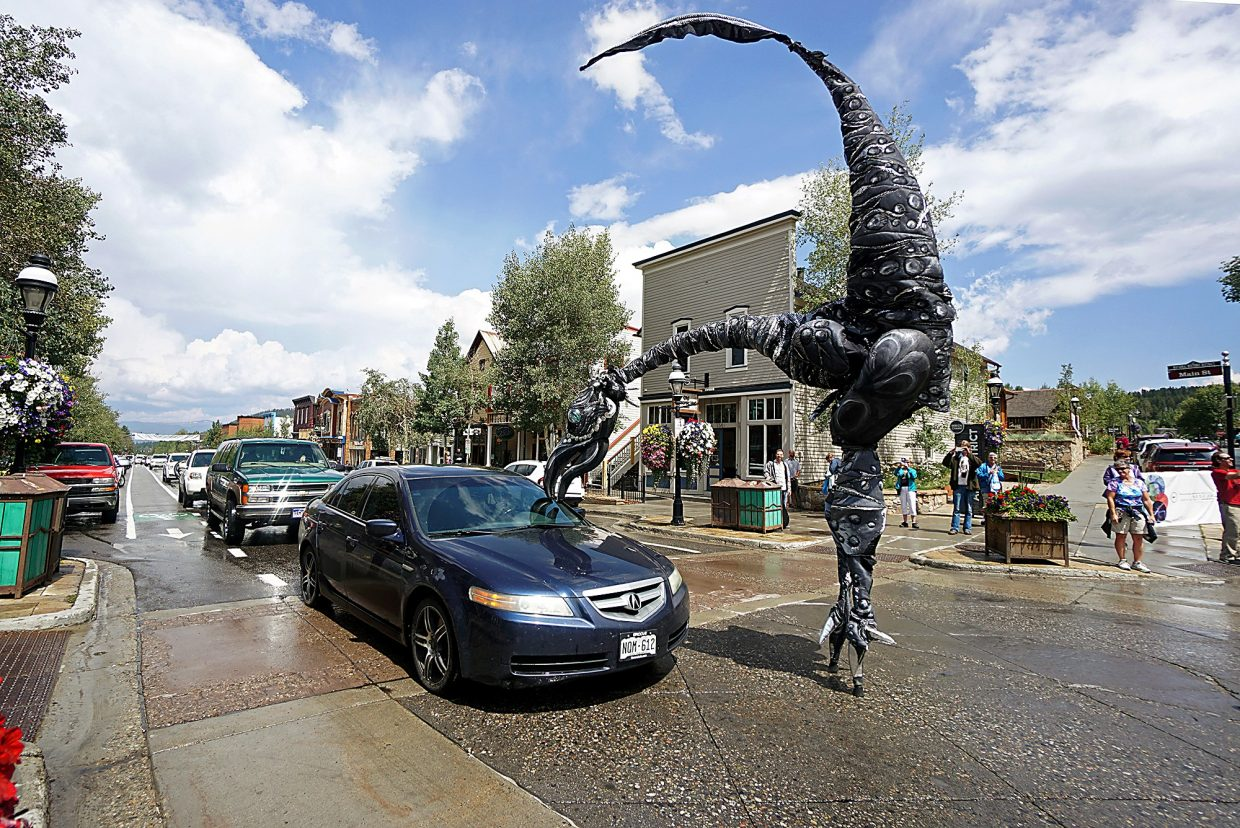 The Dutch street theatre act Saurus, which includes performers on stilts and 18-foot dinosaur costumes, interacts with cars on Main Street in Breckenridge as part of the Breckenridge International Festival of Arts Friday, Aug. 19, 2016.