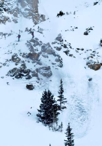 A slide triggered by explosives rolls down the slope at Tree Chutes, a section of terrain on the far north end of the East Wall at Arapahoe Basin. High above the slide on the ridge are two ski patrollers who placed the charges by hand.