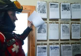 Veteran ski patroller Louis Skowyra with a display of 12 route maps at Patrol Headquarters on the summit of Arapahoe Basin. As mandated by the Bureau of Alcohol, Tobacco and Firearms, Skowyra and other snow safety patrollers use the maps to keep track of terrain where explosives are used.