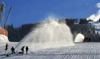 Beaver Creek race crew members, ski patrollers and volunteers work together to hose down the Red Tail Jump on the World Cup ski race course with water Saturday in preparation for this week's women's races at Beaver Creek.