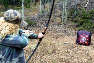 The author practices bow technique with a target before heading into the field.