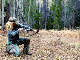 The author practices bow hunting from a kneeling position. Bow hunting requires stability and patience, just like any type of hunting, but bow hunters usually have to be much closer than rifle hunters for a kill.