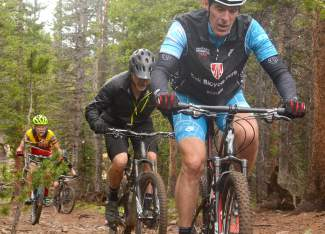 A train of mountain bikers led by Breckenridge local Craig Cooper (front) and mayor Eric Mamula (middle) power up a stretch of the Nightmare on Baldy trail during a lunch loop for Breck Bike Week in June.
