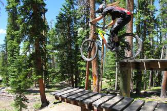 Tyler Mitchell with the Keystone Bike Park trail crew drops the log bridge on TNT, one of more than a dozen black and double-black trails at his home mountain.