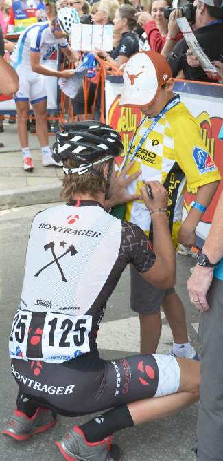 A member of the Bontrager Cycling Team signs a young fan's jersey before the Stage 3 start at the 2013 USA Pro Challenge in Breckenridge.