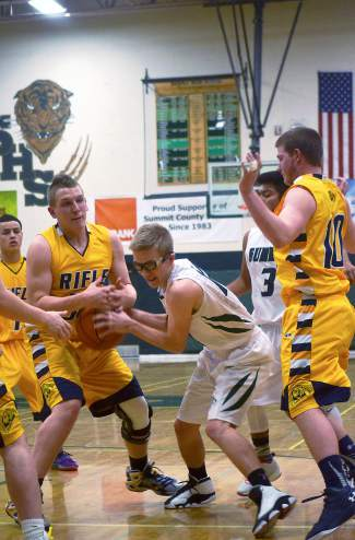 Summit senior Riley Beck (11) gets swarmed by Rifle defenders during a home basketball game on Jan. 29. The Tigers lost, 51-67.