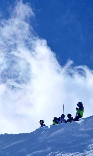Ski club coaches and athletes watch from a cornice on Peak 6 as snow whips high above at the 2016 GoPro Big Mountain Challenge on March 19. The three-day competition was shortened to two days after a weeklong storm continued to bring snow, wind and zero visibility to Breckenridge on March 18.