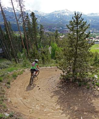 A mountain biker weaves through the Carter Park switchbacks with Breckenridge Resort in the background during a group ride for Breck Bike Week on June 23.