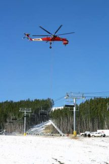 An American twin-engine heavy-lift helicopter called a Sikorsky S-64 Skycrane, places a lift tower on the Peak 6 Kensho chairlift on Tuesday. The tower installers were on track to finish placing all of the Peak 6 lift towers.