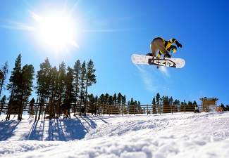 A snowboarder jumps in the freestyle park during Breckenridge Ski Resort's season opening day Friday.