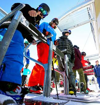 Skiers and snowboarders load onto the Colorado SuperChair at Breckenridge Ski Resort during the 2015-16 season opening day Friday.
