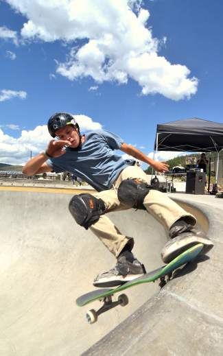 A competitor in the Battle on the Blue skateboard competition takes a smith grind around the coping of the big bowl at the Breck skate park.