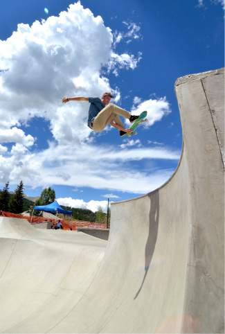 A competitor tweaks an air out of the snake bowl at the first annual Battle on the Blue skateboard contest at the Breck skate park on July 23.
