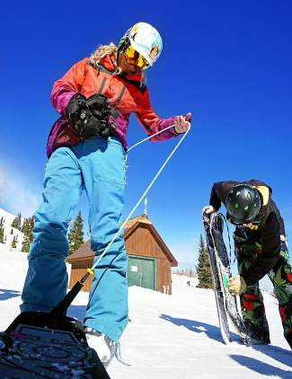Snow skater Angelica Clemmer adjusts her leash before a run at Breckenridge Ski Resort Feb. 17.