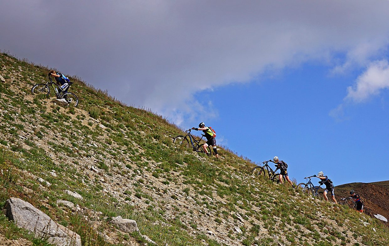 Racers hike their bikes up the final steep push toward Wheeler Pass during Stage 5 of the Breck Epic Thursday, Aug. 18, 2016.