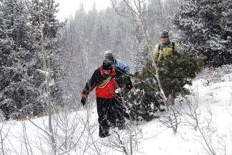 Silverthorne resident Katy Sinclair, right, along with her in-laws, Jinny, left, and Carol Sinclair, who are mother and daughter visiting from Pennsylvania, carry out their freshly-cut Chrismas Tree from the National Forest tree cutting area near the I-70 scenic overlook Sunday morning. Permits will be available starting Monday, Nov. 25 at the Dillon Ranger District office, 680 Blue River Parkway in Silverthorne.