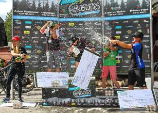 Winners in the women's pro division celebrate with champagne, beer and the mandatory massive checks after the Keystone Big Mountain Enduro race on July 12.
