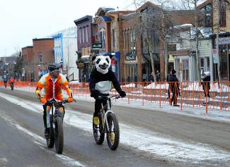 Nick Frey (right) of Boo Bicycles rides through downtown Breckenridge in full panda garb during the Fat Bike Eliminator on Jan. 14 before the Ullr Fest parade.