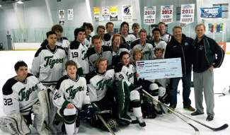 The Summit High School boys hockey team and coaches pose with a check from the 9280 Pond Hockey Tournament fundraiser after the team's final game last week. The Tigers raised more than $3,000 for the club.