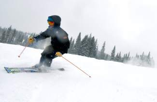 A skier makes rare early-season powder turns on Main Vein at Copper Mountain for opening day. After delaying the opener by a week, the resort saw 14 inches of snow in several days and another 7 overnight before first chair.