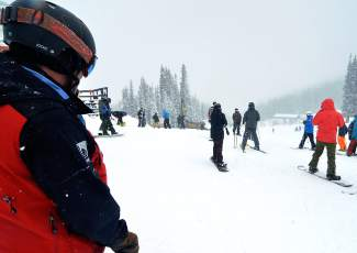 A ski patroller watches skiers and snowboarders enjoy first turns on opening day at Copper Mountain Nov. 11.