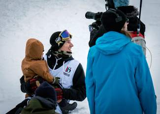 Snowboarder Chas Guldemond of Truckee gets a hug from his child while waiting for his score after the men's Dew Tour snowboard slopestyle semifinal on Dec. 10. Guldemond went on to finish seventh in the final.