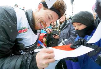 Shaun White signs autographs for fans following his Dew Tour men's snowboard superpipe competition win at Breckenridge Ski Resort Saturday.