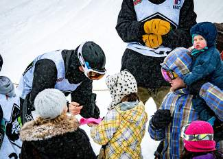 Shaun White signs autographs for young fans between practice runs before the snowboard halfpipe finals at Dew Tour.