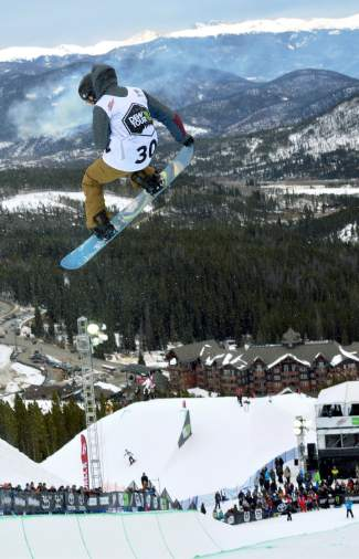 A competitor in the Dew Tour snowboard halfpipe semifinal at Breckenridge spins with burn pile smoke far in the background. The town of Breckenridge performs forest maintenance throughout the year to manage deadfall from beetle-kill pine infestation.