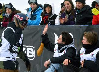 Ben Ferguson, left, gives a high-five to fellow rider Brett Esser, middle, sitting with Taylor Gold at the bottom of the halfpipe at Breckenridge. All three earned a spot in the final at 12:30 p.m. on Dec. 12.