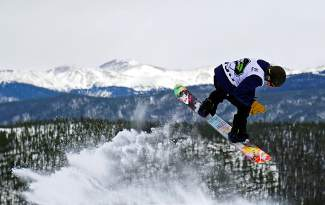A snowboarder takes off from a jump during the Dew Tour men's slopestyle semi-finals at Breckenridge Ski Resort Friday.